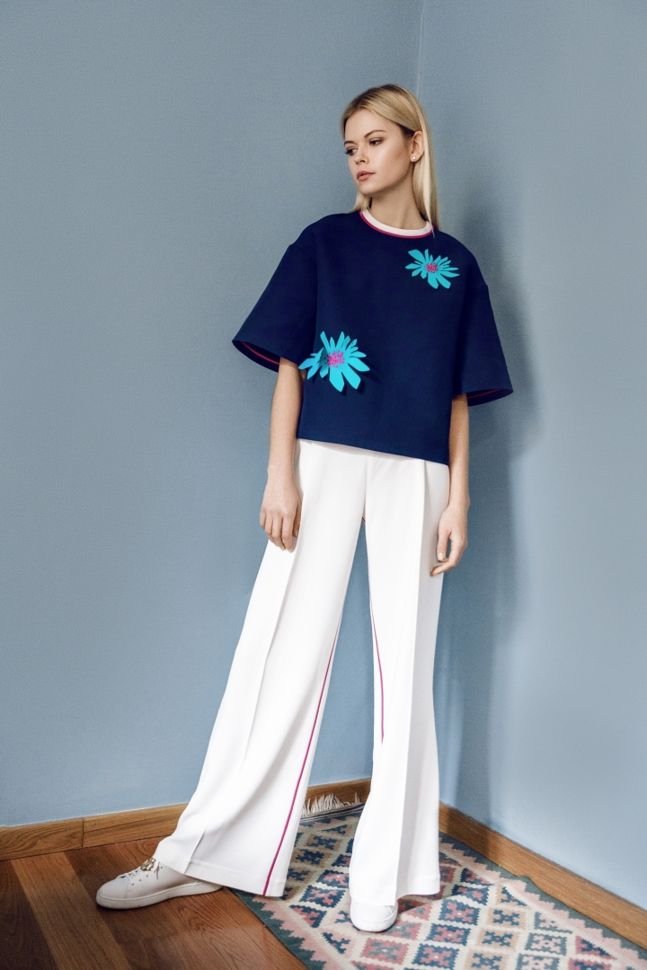 A Korsun Navy Blue Top with floral details paired with Korsun white wide leg pants.